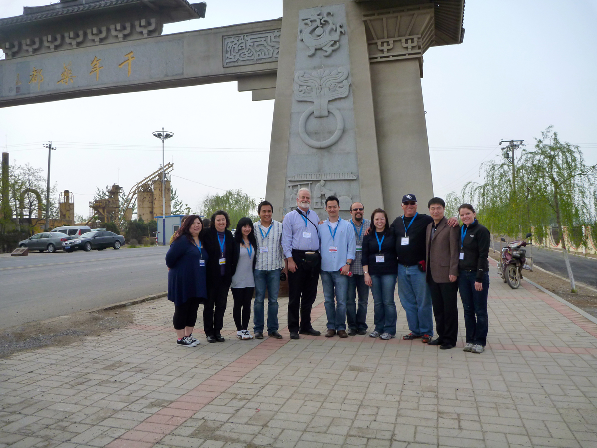 Mayway staff at the arch over the entrance to Anguo